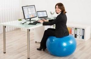Une femme qui travaille au bureau avec une balle de Pilates.