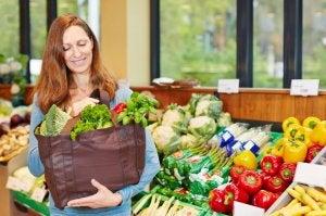 Femme qui fait ses courses avec un panier de fruits et légumes.