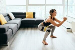 Une femme fait des squats dans son salon