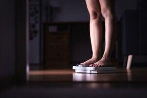 Femme qui se pèse sur une balance.