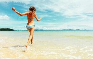 Une femme à la plage avec les pieds dans l'eau.