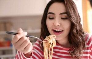 Une femme mange des pâtes