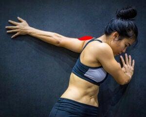 Une femme étire les épaules contre un mur