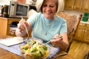 Une femme âgée qui mange une salade.
