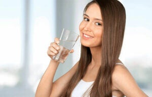 Une femme qui boit un verre d'eau.