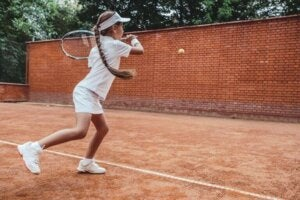 fille jouant contre un mur au tennis