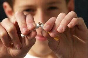 Un garçon casse une cigarette