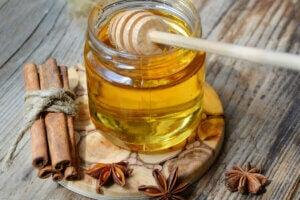 Pot de miel avec des bâtons de cannelle.