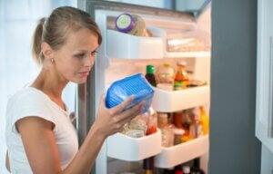 Une femme qui vérifie un aliment périmé au frigo.