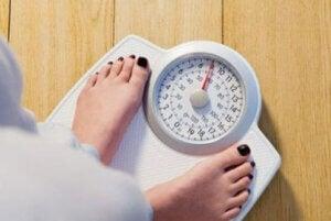 Une femme qui contrôle son poids sur une balance.