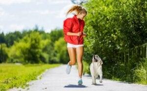 Une femme qui court dans un parc avec son chien