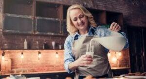 Une femme qui sert un verre de lait.