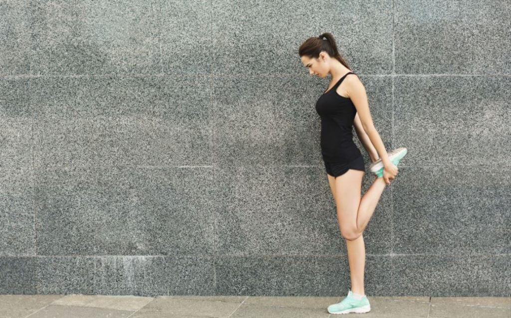 Une jeune femme qui étire les quadriceps.