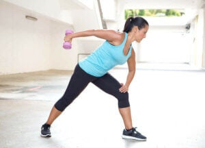 Une femme qui exerce ses triceps pendant le télétravail