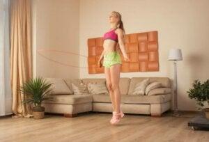 Une jeune femme qui fait du saut à la corde dans sa maison.