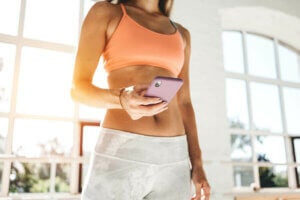 Une femme qui fait de l'exercice chez elle à l'aide d'une application sur son téléphone.