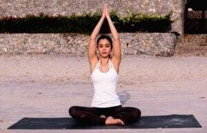Femme en position indienne sur un tapis de yoga.