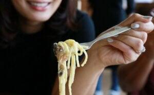 Une femme qui mange des spaghettis.
