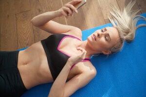 Une jeune femme qui fait de l'exercice avec une application téléphonique.