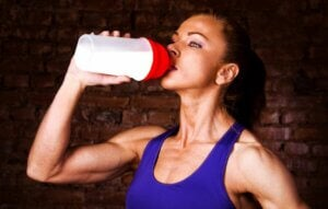Une femme qui boit une boisson protéinée.