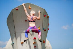 Une femme qui escalade un mur urbain.