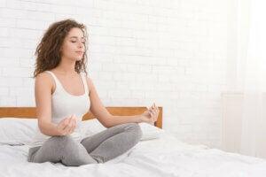 Une jeune femme qui médite chez elle.