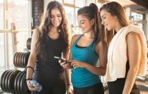 Trois jeunes femmes sportives qui regardent un téléphone.
