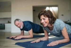 Un couple de personnes âgées qui fait de l'exercice à la maison.