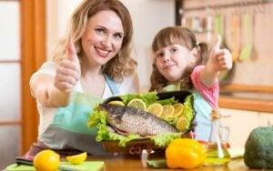 Une maman et sa fille devant un plat de poisson.