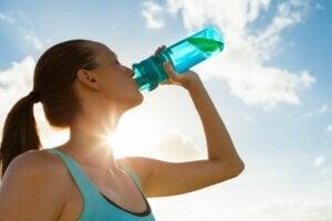 Une femme sportive qui boit de l'eau.