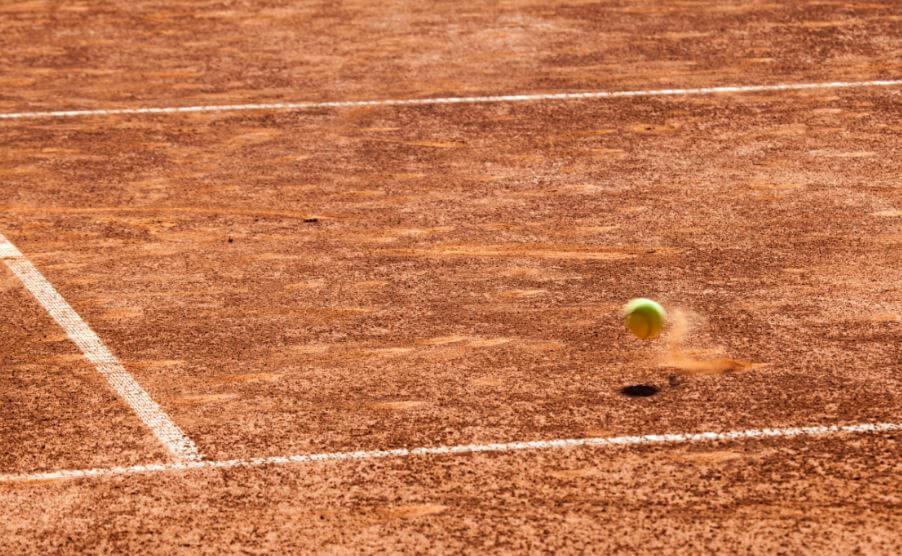 balle de tennis rebondissant sur de la terre battue