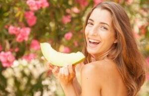 Une femme qui mange une tranche de melon.