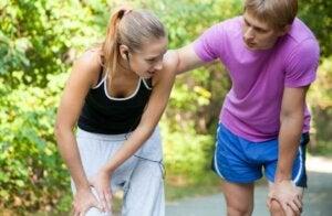 Un couple qui fait du sport en plein air, la femme a mal au genou.