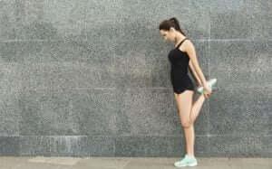 Une femme qui s'étire les quadriceps.