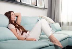 Une femme qui se repose sur son canapé.