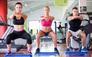 Trois personnes qui font des squats dans une salle de sport.