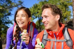 Un couple en randonnée qui mange une barre énergétique.