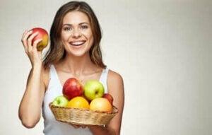 Une femme tenant un panier de pommes.