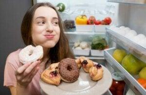 Une jeune femme qui mange des donuts dans le frigo.