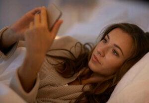 Une femme au lit avec son téléphone.