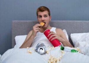 Un homme mangeant de la malbouffe dans son lit.