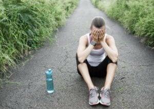 Une joggeuse effondrée assise par terre.