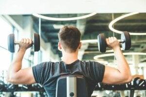 Un homme qui muscle ses épaules et ses bras dans une salle de sport.