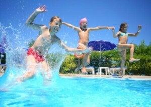 Trois enfants qui sautent dans une piscine.
