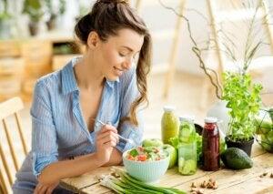 Une femme qui mange une salade.