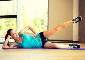 Une femme fait des balancements de jambe.