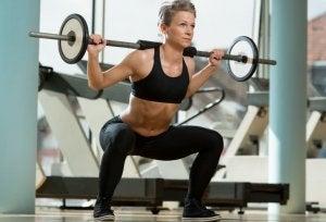 donna che solleva peso facendo squat