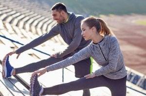 uomo e donna che si riscaldano con stiramenti delle gambe prima di correre