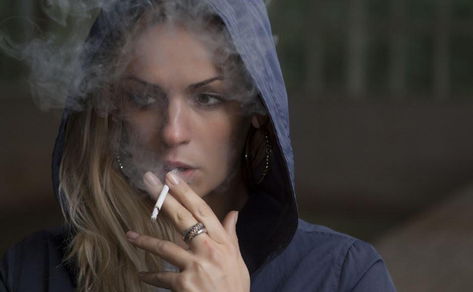 ragazza con cappuccio che fuma