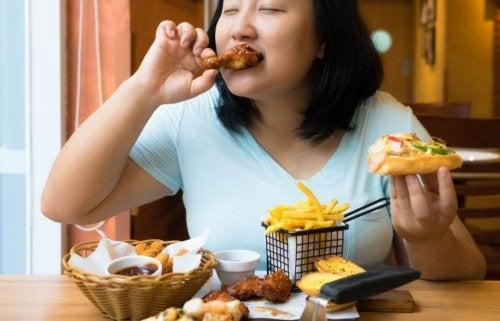 Donna che mangia del cibo spazzatura
